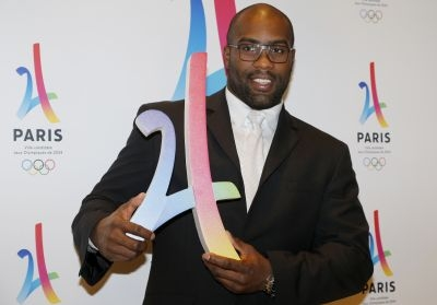 French judoka Teddy Riner poses with the logo of Paris as candidate for the 2024 Olympic summer games during a press conference in Paris on February 17, 2016. The race to host the 2024 Olympic Games gets underway in earnest today with the four bid cities -- Budapest, Los Angeles, Paris and Rome -- presenting their initial candidature files to the International Olympic Committee (IOC).