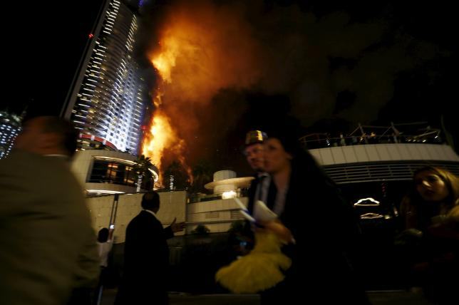 People run away as a fire engulfs The Address Hotel in downtown Dubai in the United Arab Emirates December 31, 2015. REUTERS/Ahmed Jadallah