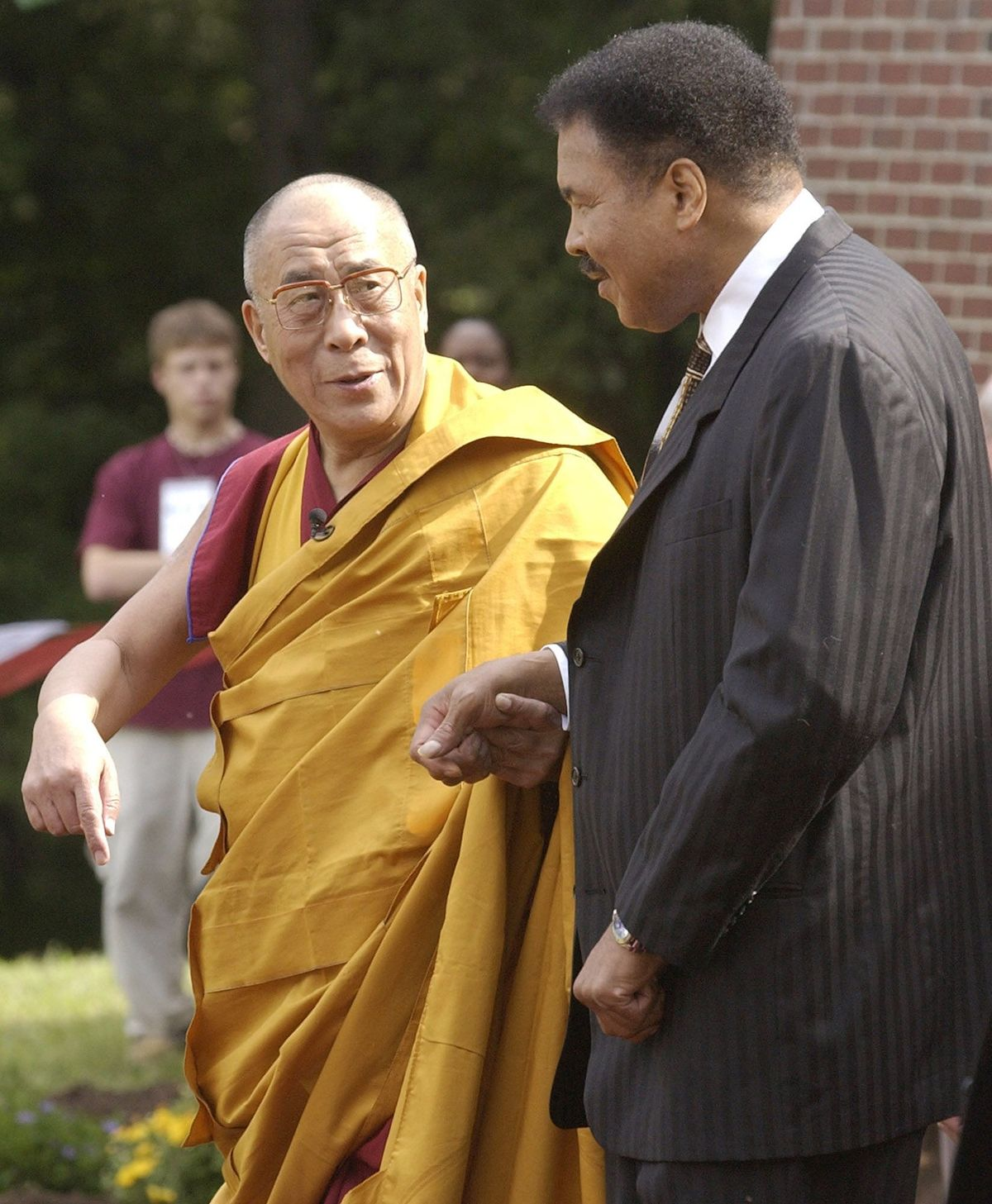 The Dalai Lama walks with Ali as they move towards a new interfaith temple at the Tibetan Cultural Center in Bloomington, Indiana, 2003.