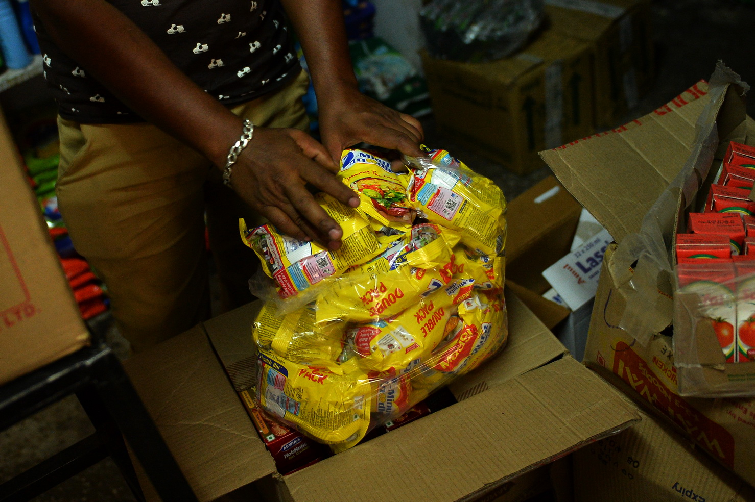 In this photograph taken on June 17, 2015, an Indian shopkeeper puts packs of Nestle 'Maggi' instant noodles into a plastic bag in his shop in New Delhi.  Nestle chief Paul Bulcke said that he wanted to see its hugely popular Maggi brand of instant noodles back on the Indian market as soon as possible after it was banned over a health scare. India's food safety regulator on June 5 banned the product after tests that it said showed the noodles contained excessive levels of lead.  AFP PHOTO/Chandan KHANNA