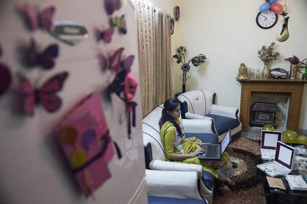 """TO GO WITH 'Pakistan-Economy-Internet-Commerce' FOCUS by Masroor GILANI This photograph taken on November 18, 2015 shows Pakistani Nosheen Kashif, an employee of online marketplace company Kaymu, working on a laptop at her residence in Islamabad. Women are seeing the benefits, but e-commerce presents potentially an even greater opportunity for young people in a country where roughly two thirds of the population -- of around 200 million -- are estimated to be under the age of 30. A recent economic survey by the finance ministry singled out the challenges facing youth in Pakistan, including """"limited job search expertise, a mismatch between education, aspirations and employers' requirements and a lack of mobility, among other factors"""". AFP PHOTO / Aamir QURESHI / AFP / AAMIR QURESHI"""