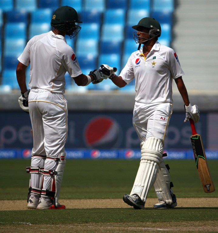 Pakistan's Younis Khan (R) greets his teammate Shan Masood during the first day of the second Test cricket match between Pakistan and England in Dubai on October 22, 2015.       AFP PHOTO/MARWAN NAAMANI