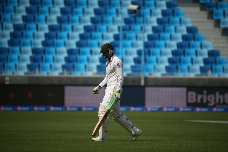 Pakistan's Mohammad Hafeez walks from the pitch after he was dismissed during the first day of the second Test cricket match between Pakistan and England in Dubai on October 22, 2015.       AFP PHOTO/MARWAN NAAMANI